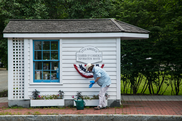 Woman watering flowers at the Chamber of Commerce in Stockbridge.